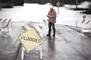 "Man in orange jacket standing next to flooded area near ""flooded"" sign"