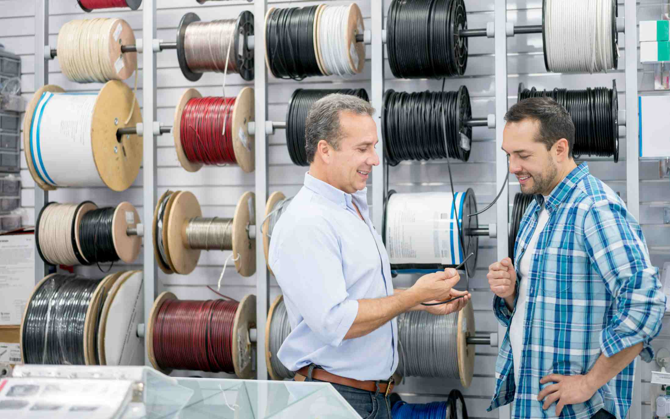 Salesperson talking to shopper in front of wall holding several spools of wire in a hardware store.