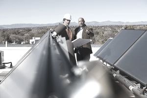 Business owner and construction worker looking at solar panels