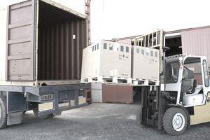 Forklift with boxes by open truck