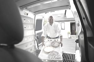 Catering chef loading food into van