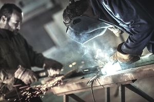 Factory workers doing metal work in protective clothing