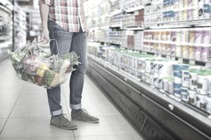 Lower-body view of a man holding a basket of groceries at the grocery store, browsing products on cooler shelves