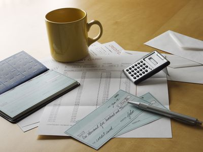 Papers, a check book and check written by a small business owner for taxes laying on a desk.