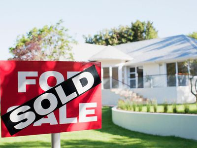 Sold sign in front yard of house