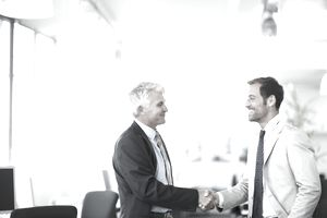 Attorney on retainer shaking hands with his client in an office setting.