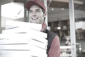 Pizza delivery driver carrying a stack of pizza boxes from a store.