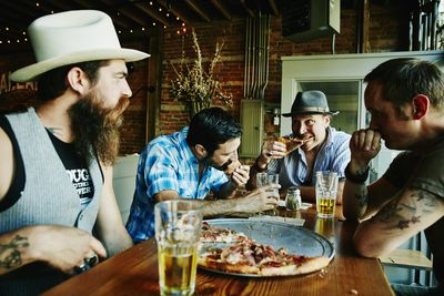A local business establishment serves friends beer and pizza.