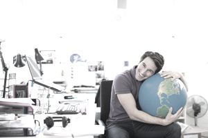 Smiling businessman hugging globe at desk in office