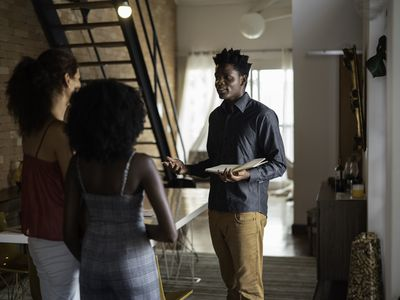 A man holds a notebook while taking two women on an apartment tour