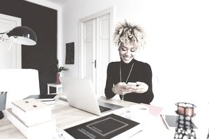 Beautiful afro american young woman sitting at the desk in a home office and using a smart phone.