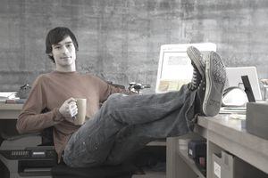 sole proprietor sitting in office with feet on his desk