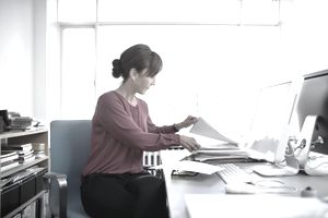 woman organizing documents at her desk