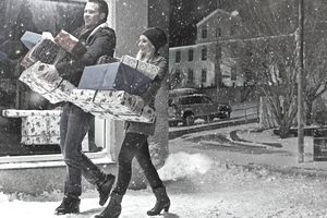 Couple with Christmas gifts in snow