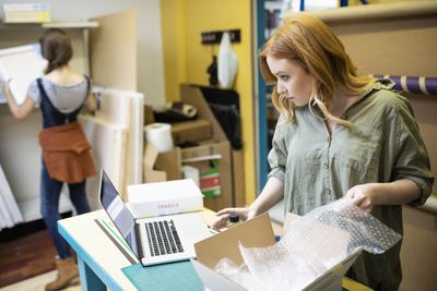 Woman packaging while on computer