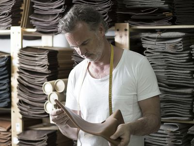 Man working in leather factory determining the cost of objects