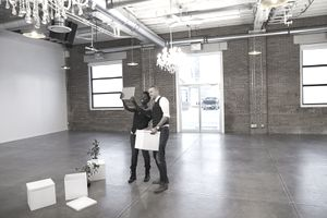 Businessman and Businesswoman Taking Selfie With Digital Tablet Camera in Empty New Office