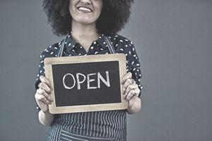 "Studio shot of a young woman holding a chalkboard with the word ""open"" on it against a gray background"