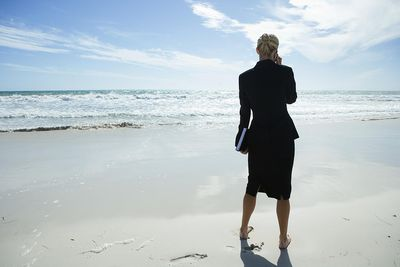 Business woman standing on a beach next to the ocean.