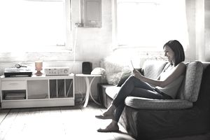 Woman sitting on couch reading tablet