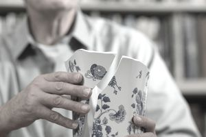 Mature man sitting at table repairing broken china vase.