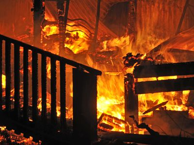 flames and smoke rise from burning house