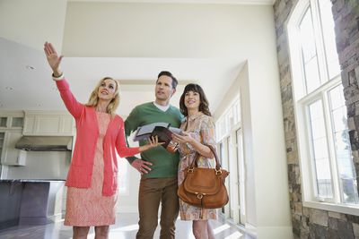 Female realtor showing home to couple