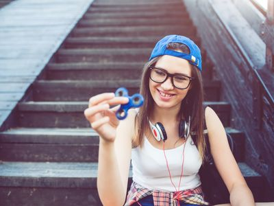 Teen girl sitting on steps playing with fidget spinner