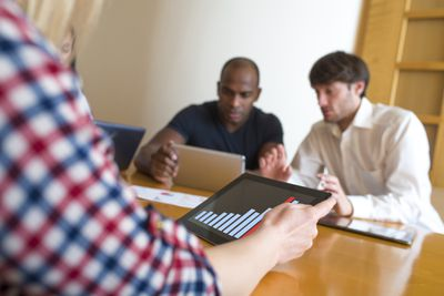 Woman holding an iPad with bar graph on it with two men looking at ipad in the back ground
