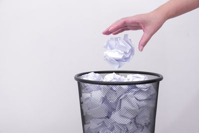 Hand throwing out trash in bin