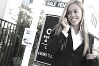 "Real estate agent talking on a cellphone in front of a ""for sale"" sign"