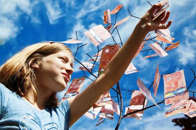 A girl picking Canadian 50 dollar bills off of a tree