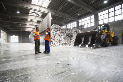 Workers in paper recycling hall with waste paper