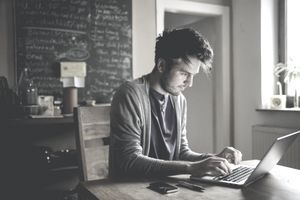 A writer working remotely typing on a laptop computer at his dining table.