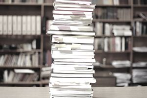 Tall pile of books on a desk, sticky notes marking pagespages