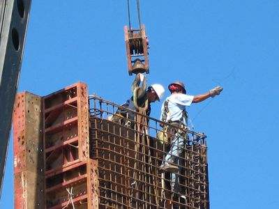 Construction workers setting rebar frame high up on a tower next to a heavy crane hook.