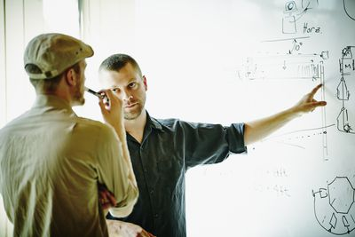 Two engineers discussing project design in office