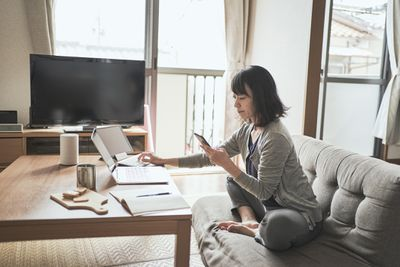 A woman fits on her couch, looking at a phone while working on two laptops running a virtual assistant business