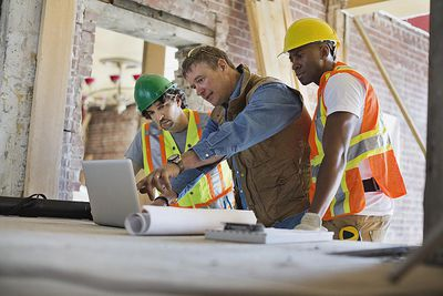 A contractor discussing plans with workers