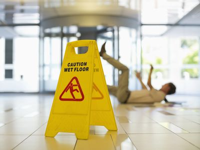 Caution Wet Floor sign in a lobby with a man who slipped laying on the floor in the background