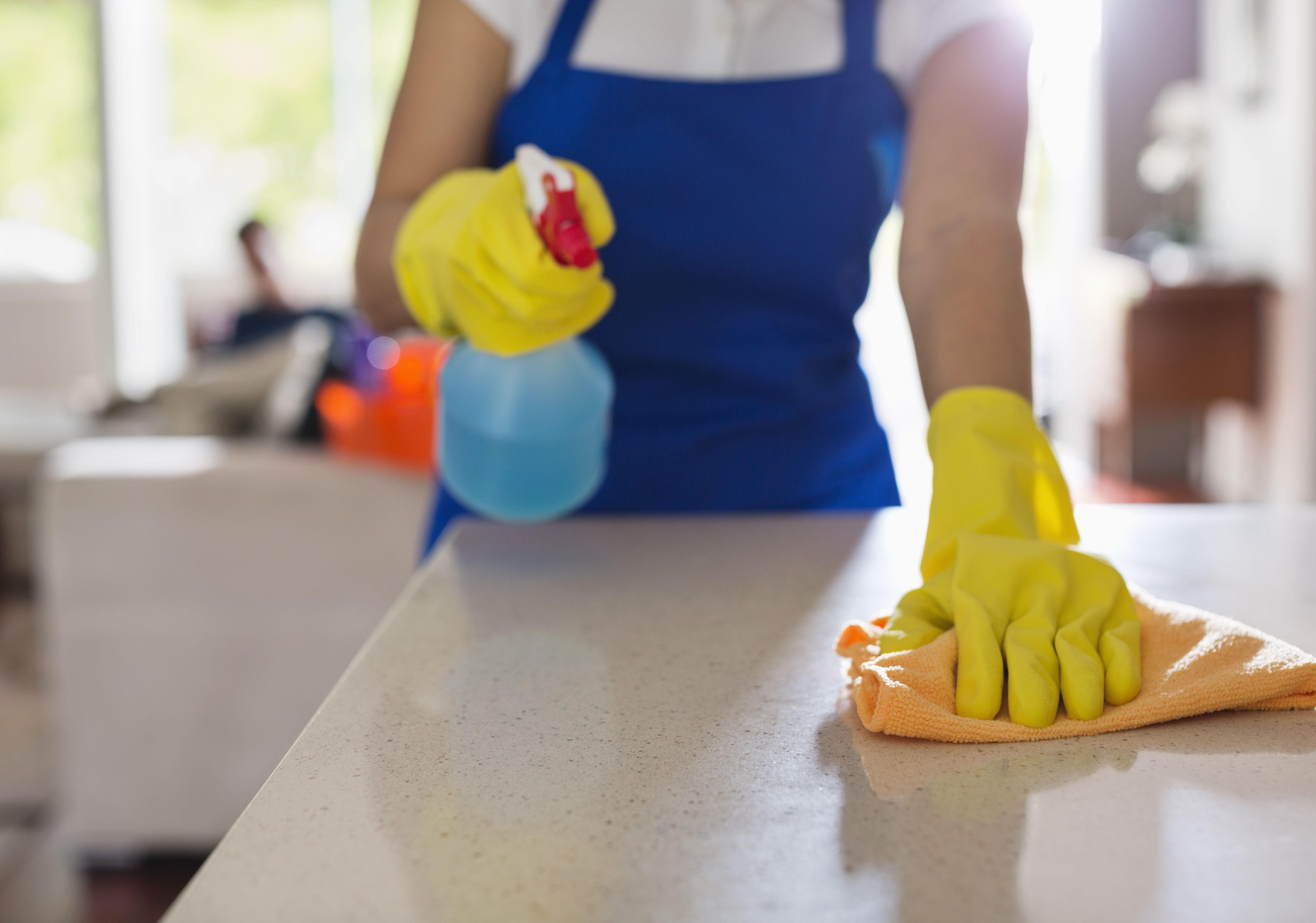Close-up of woman's gloved hands cleaning kitchen counter