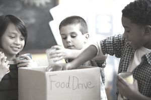 "Children gathered around a box labeled ""food drive"""