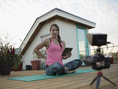 Female yoga instructor with digital tablet and video camera filming, vlogging on yoga mat on deck patio