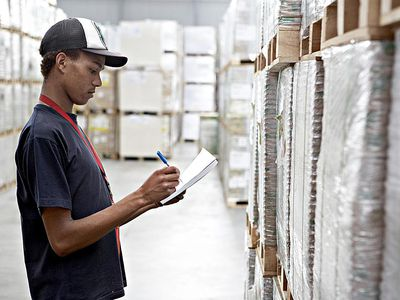 a man taking inventory in a warehouse