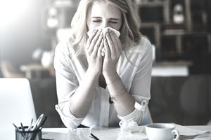 Woman blowing her nose who is sick
