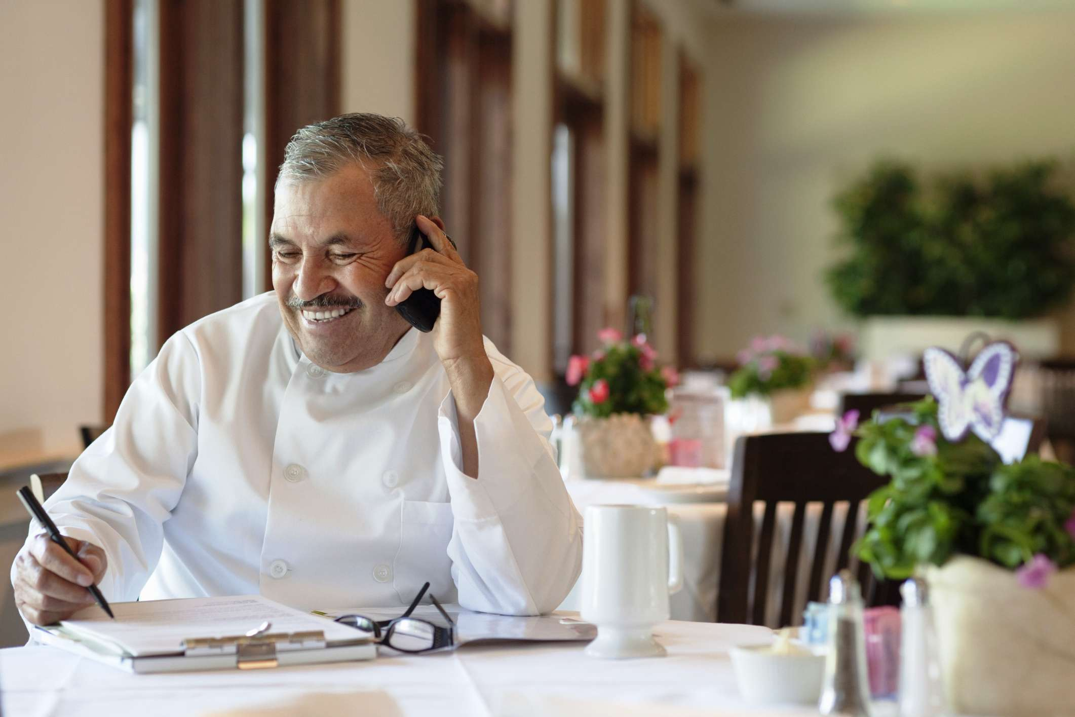 Chef filling out orders while on the phone