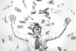Smiling businessman with dollar bills in the air around him representing his gross profit margin.