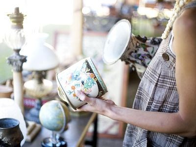 A woman looking at vases in antique store
