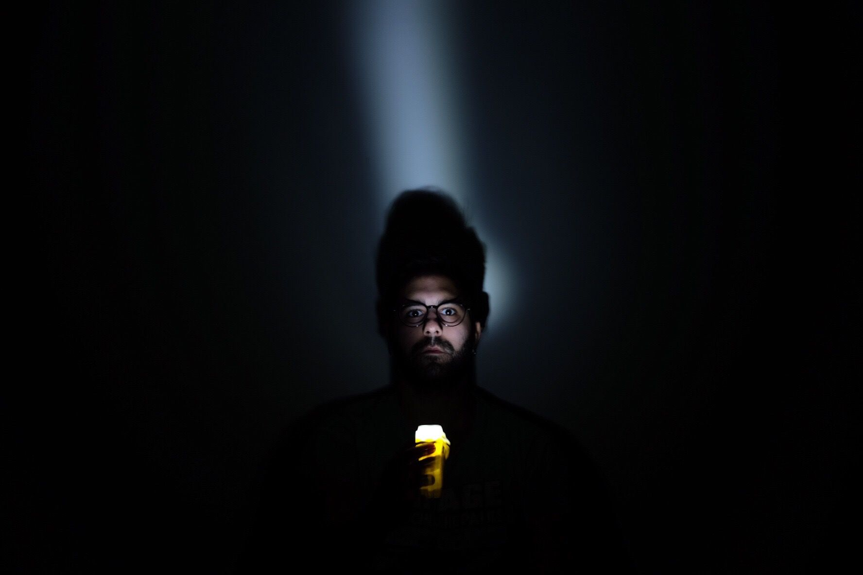 Man holding a flashlight to his face during a power outage.