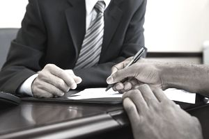 man signing loan document in front of banker